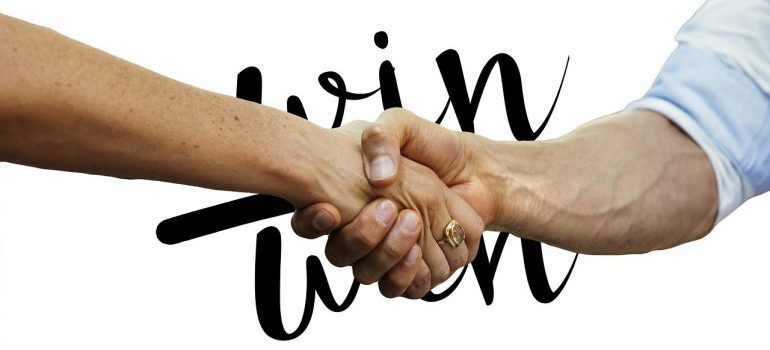 "A handshake with ""win - win"" written in the background"