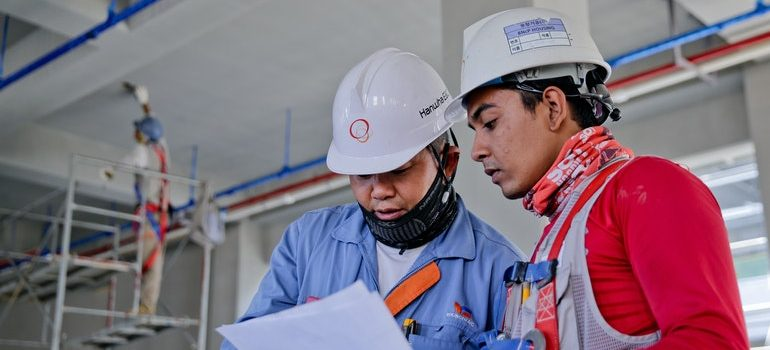 Two construction workers reading papers.