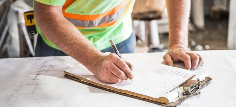 Construction worker writing on a clipboard.