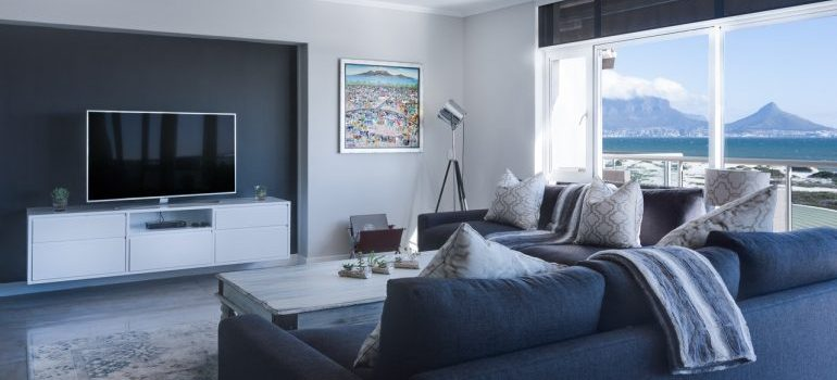 A living room with a blue couch and white furnishings.