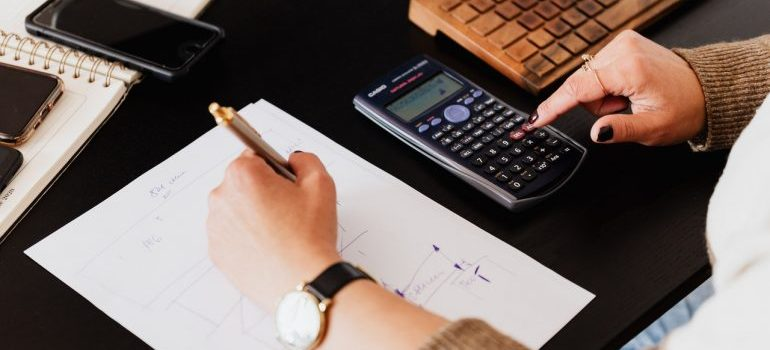 A person calculating and writing