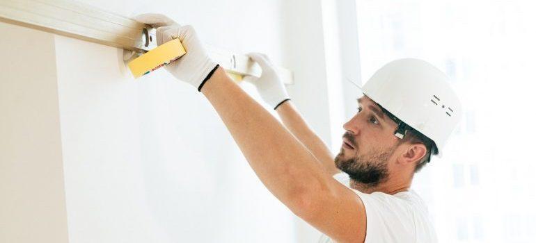 A contractor in a white attire measuring a wall.