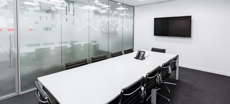A conference room separated from the rest of the office with a glass divider, representing ways to make an office design more efficient.