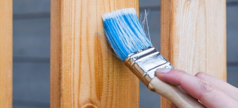 A person using a paintbrush on a wooden beam.