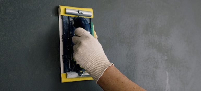 hand scraping a wall