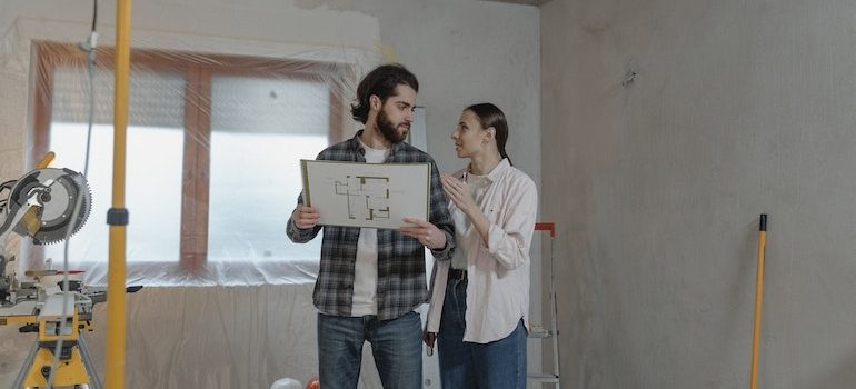 man and woman looking at plans in a construction site